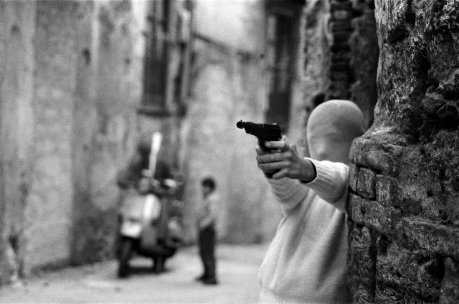 "(EN) Film subject Letizia Battaglia's photo Palermo, 1982. Vicino alla Chiesa di Santa Chiara. Il gioco del killer. (""Palermo, 1982. Near the Church of Santa Chiara. The game of the killer."") in Shooting the Mafia, directed by Kim Longinotto. Courtesy of Lunar Pictures."