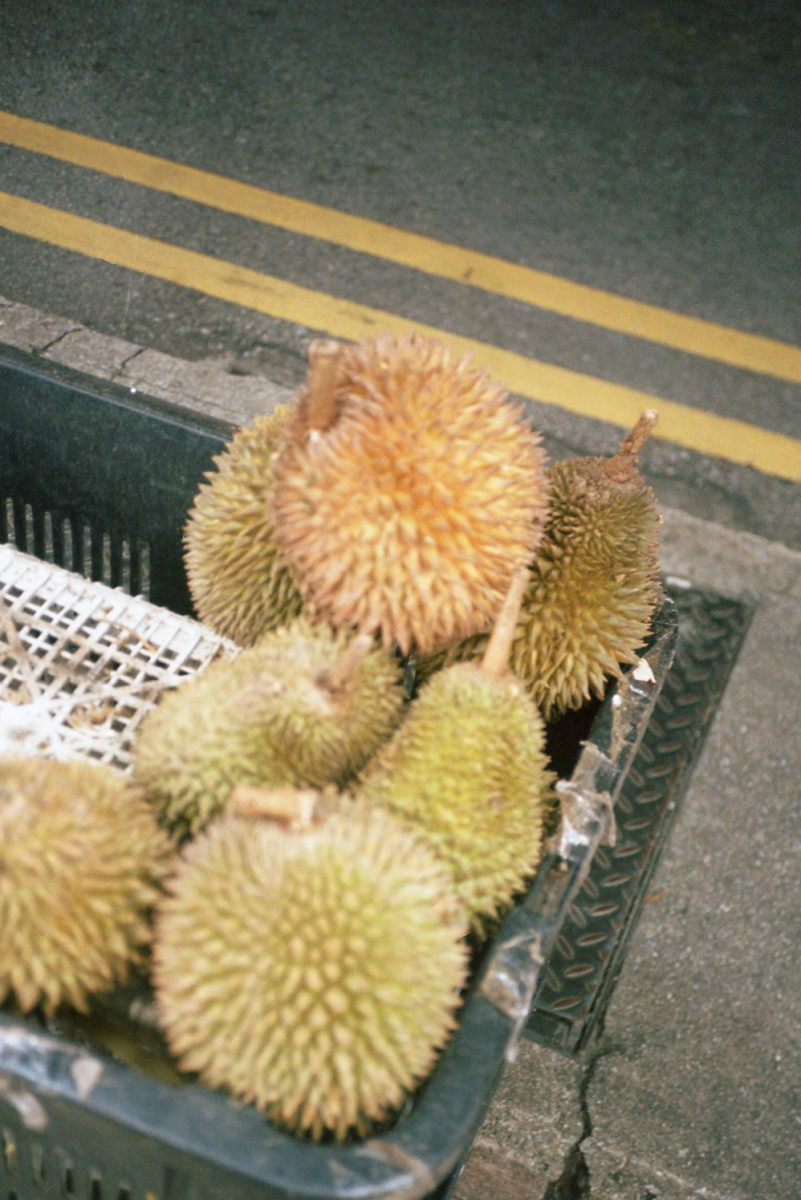 "(EN) ""This is probably the most iconic subject amongst the photographs—the durian. This is a fruit that, in all its beauty (and intensity), divide people into two camps: lovers and haters. I proudly belong to the first camp and have fond memories of gathering round a roadside table under the fluorescent lights in the cool night air feasting on its custard-like flesh."""