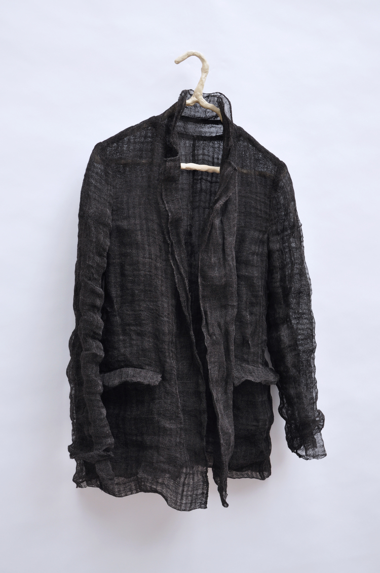 (EN) Stainless steel and virgin wool, double layered jacket with sculptural sleeves to pull half up, half down; extremely fine stainless threat wraps around each thread of virgin wool, giving the piece a